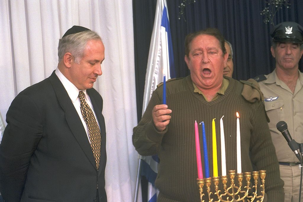 1024px-Flickr_-_Government_Press_Office_(GPO)_-_P.M._BENJAMIN_NETANYAHU_LISTENING_TO_THE_CHIEF_IDF_CANTOR_ARYE_BRAUN_RECITING_THE_HANUKA_BLESSING
