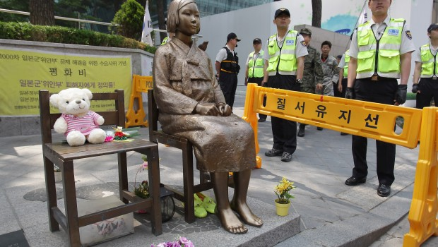 South Korean police stand guard beside a comfort woman statue in front of the Japanese embassy in Seoul in May. The Southern California city of Glendale will dedicate an identical statue on Tuesday.