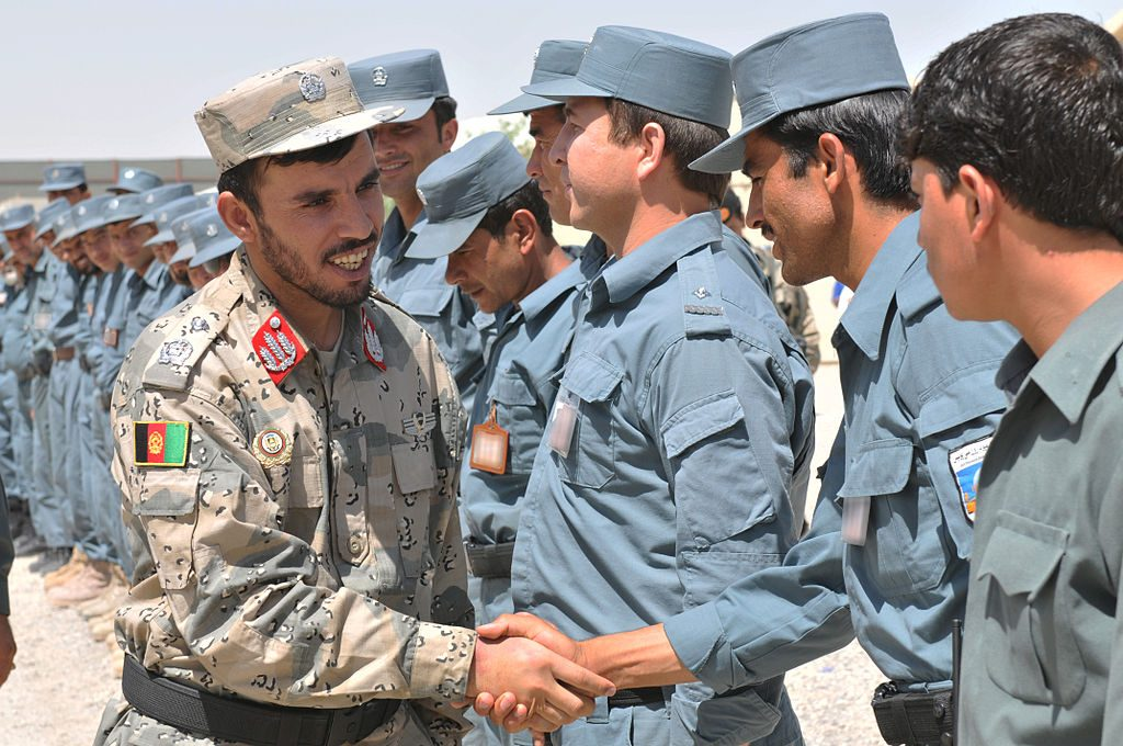 Afghan Brig. Gen. Abdul Raziq, left, Kandahar provincial chief of police, shakes hands with Afghan Uniform Police instructors at the Kandahar Regional Training Center in southern Afghanistan, Jun. 7, 2012 (Renee Crisostomo via Wikimedia Commons)
