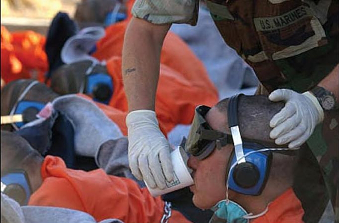 GI_gives_goggled_Guantanamo_captive_a_drink,_2002-01-11