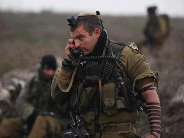 An Israeli soldier wearing tefillin, which are worn by religious Jews during morning prayers while he holds his firearm and talks with his commander