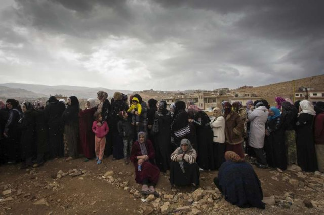 Photo: Under a striking, overcast sky, a long line of women wait to register with UNHCR in the Lebanese town of Arsal.