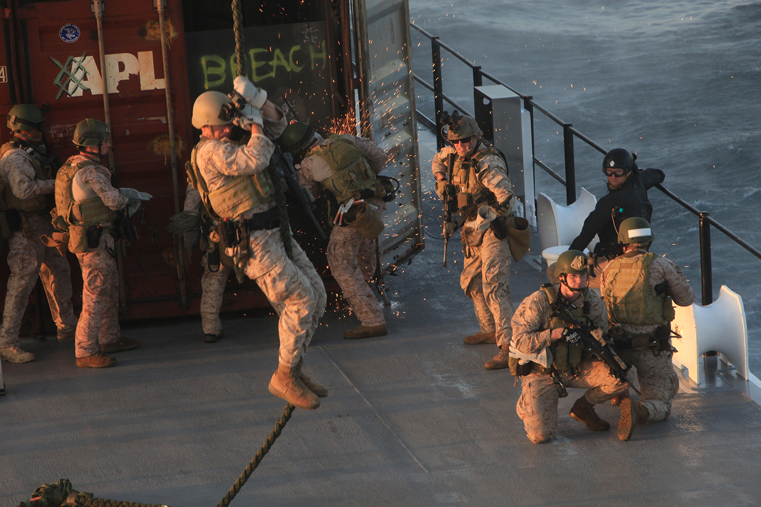 Marines with the 1st Marine Special Operations Battalion, U.S. Marine Corps Forces, Special Operations Command breach a cargo container as others rappel from a CH-47 helicopter onto the deck of a mock cargo ship during Visit, Board, Search and Seizure (VBSS) training with the 160th Special Operations Aviation Regiment near Camp Pendleton, Calif. Dec. 11. VBSS, which consists of maritime vessel boarding and searching, is used to combat smuggling, drug trafficking, terrorism and piracy. (U.S. Marine Corps photo by Cpl. Kyle McNally/Released)