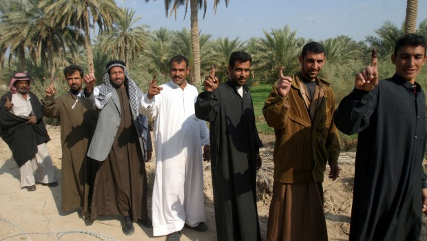 051215-M-4314O-002 Iraq (Dec. 15, 2005) Ð A group of Iraqi citizens walk down a path showing their purple fingers, signifying that they voted in their countryÕs first parliamentary election. Iraqi citizens elected their first permanent parliamentary government, which will lead the new democracy for the next four years. U.S. Marine Corps photo by Lance Cpl. Michael J. O'Brien (RELEASED)