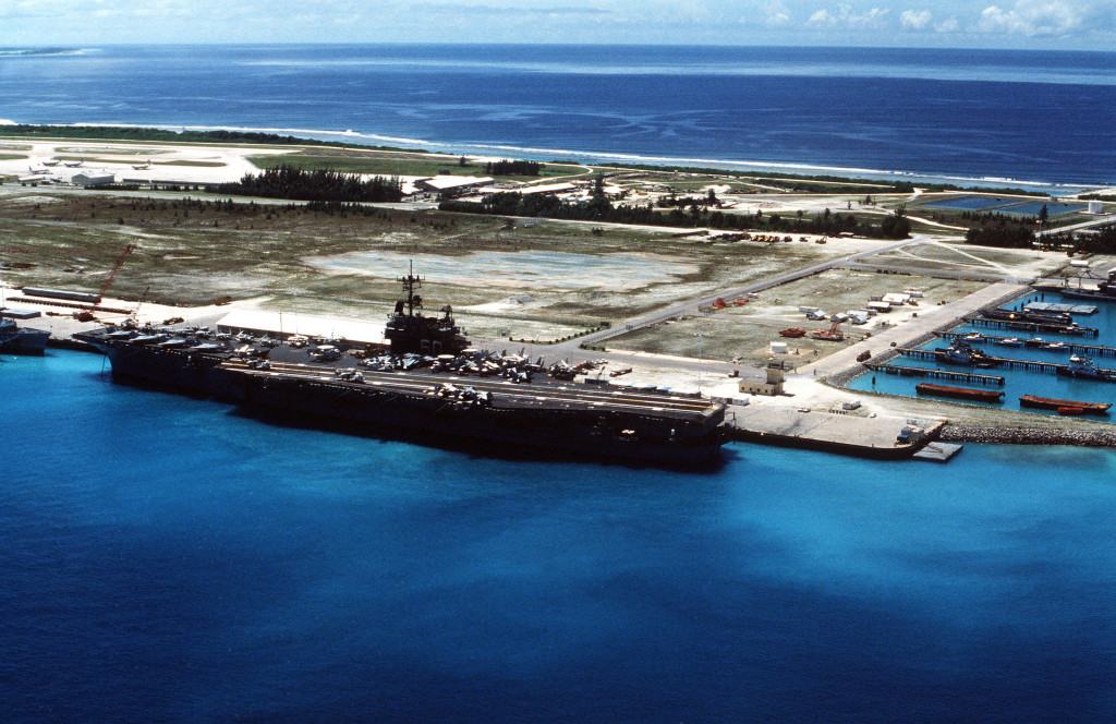 Aerial port quarter view of the Forrestal Class, Aircraft Carrier USS SARATOGA (CV 60) tied up at the British Naval Base at Diego Garcia.  The ship stopped at the British Protectorate during her 1987 deployment.  Visible on the flight deck as F-14A Tomcats, A-6E Intruders and E-2B Hawkeye aircraft.