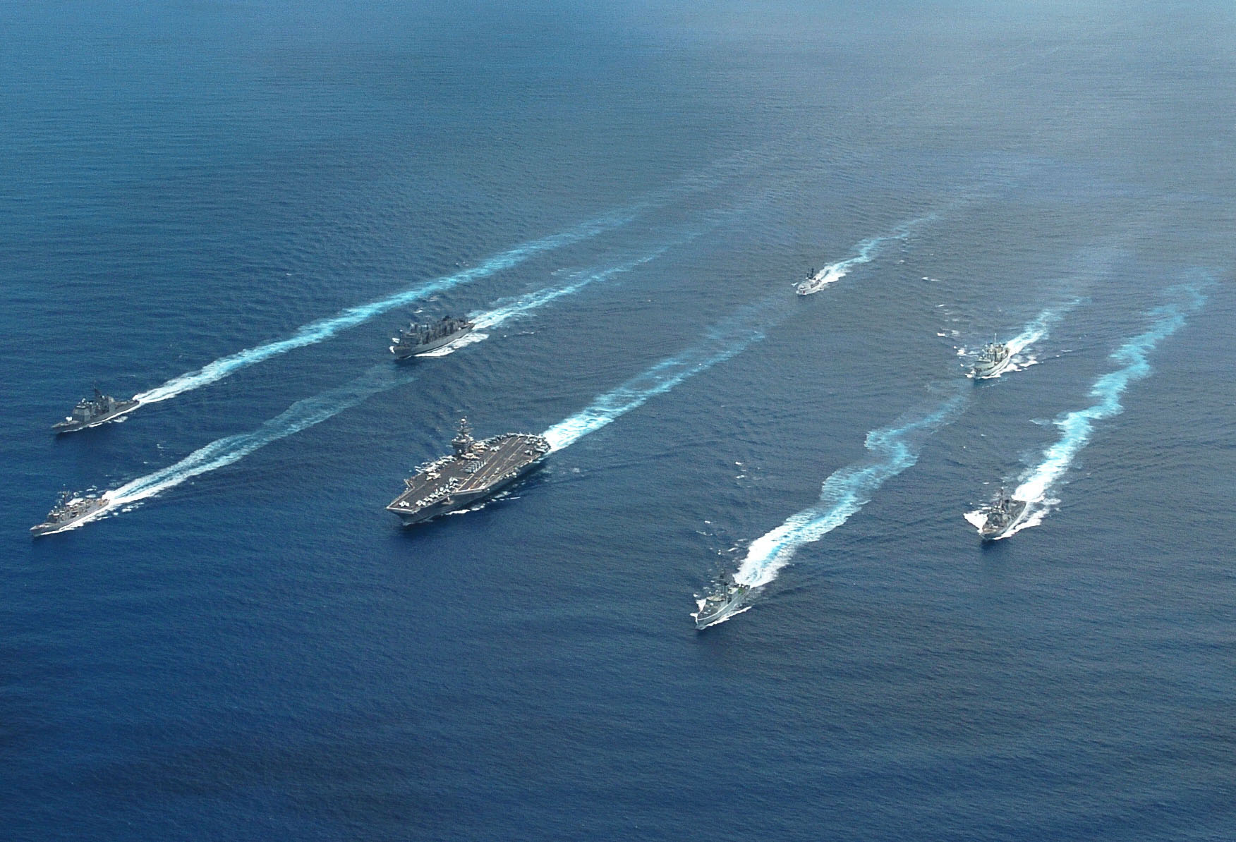 040625-N-9769P-245 Pacific Ocean (June 25, 2004) Ð Ships from the United States and Canada navigate around the aircraft carrier USS John C. Stennis (CVN 74) while underway in the Pacific Ocean during a multi-national photo exercise. Stennis and embarked Carrier Air Wing Fourteen (CVW-14) are at sea on a scheduled deployment, and is expected to participate in Rim of the Pacific (RIMPAC) 2004. RIMPAC is the largest international maritime exercise in the waters around the Hawaiian Islands.  This years exercise will include eight participating nations; Australia, Canada, Chile, Japan, Peru, South Korea, Britain and the United States.  RIMPAC is intended to enhance the tactical proficiency of participating units in a wide array of combined operations at sea, while enhancing stability in the Pacific Rim region. U.S. Navy photo by Photographer's Mate 2nd Class Jayme Pastoric (RELEASED)