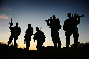 us_navy_100529-f-9200d-005_marine_sgt-_nathan_brewer_the_lead_team_mentor_for_the_drivers_training_course_stands_with_his_team_as_the_sun_sets_at_camp_shaheen_afghanistan