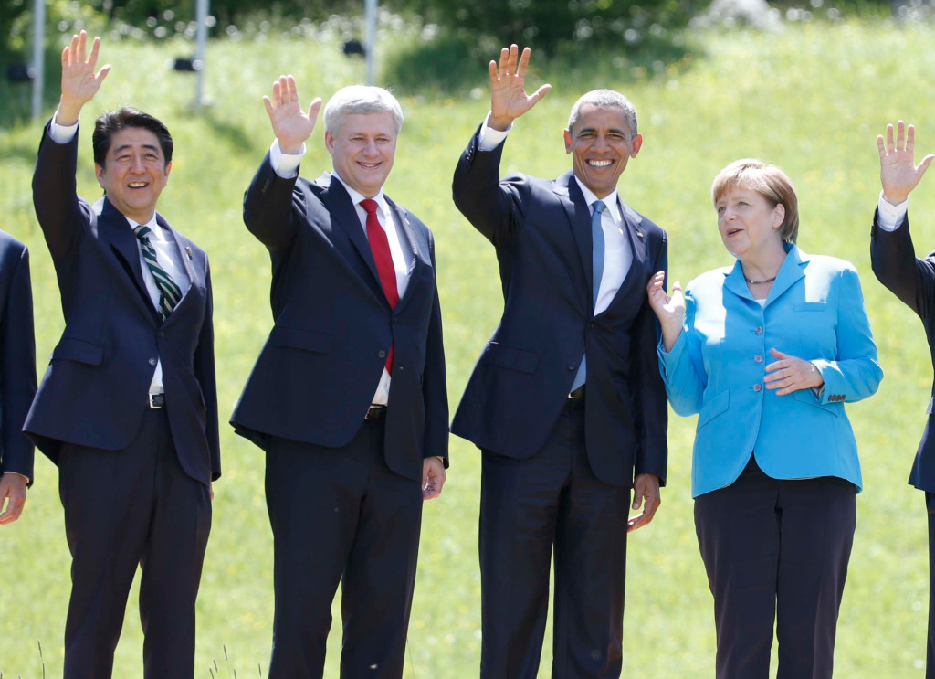 President of the European Council, Donald Tusk, Japanese Prime Minister Shinzo Abe,Canada's Prime Minister Stephen Harper, US President Barack Obama, German Chancellor Angela Merkel, French President Francois Hollande, British Prime Minister David Cameron, talian Prime Minister Matteo Renzi  and European Commission President Jean-Claude Junker (L-R) wave hands as they pose for a family photo during their meeting at the hotel castle Elmau in Kruen, Germany, June 7, 2015. Leaders from the Group of Seven (G7) industrial nations met on Sunday in the Bavarian Alps for a summit overshadowed by Greece's debt crisis and ongoing violence in Ukraine.  REUTERS/Christian Hartmann   - RTX1FHLZ