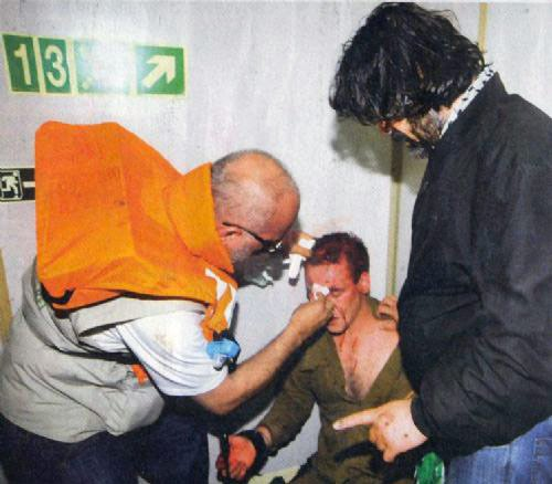 Passengers on the Mavi Marmara aid an injured Israeli soldier
