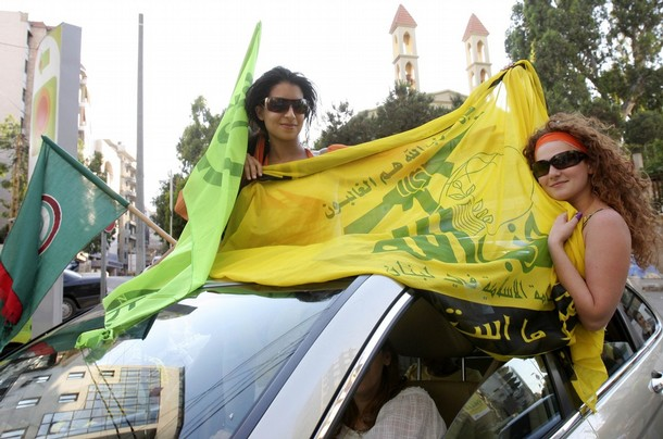 Supporters of opposition parties carry Hezbollah and opposition flags as they tour in Beirut's suburbs