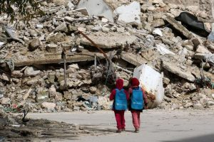 Syrian girls walk past the rubble of destroyed buildings in rebel-held Aleppo in 2015 (Jordi Bernabeu Farrús via Flickr)